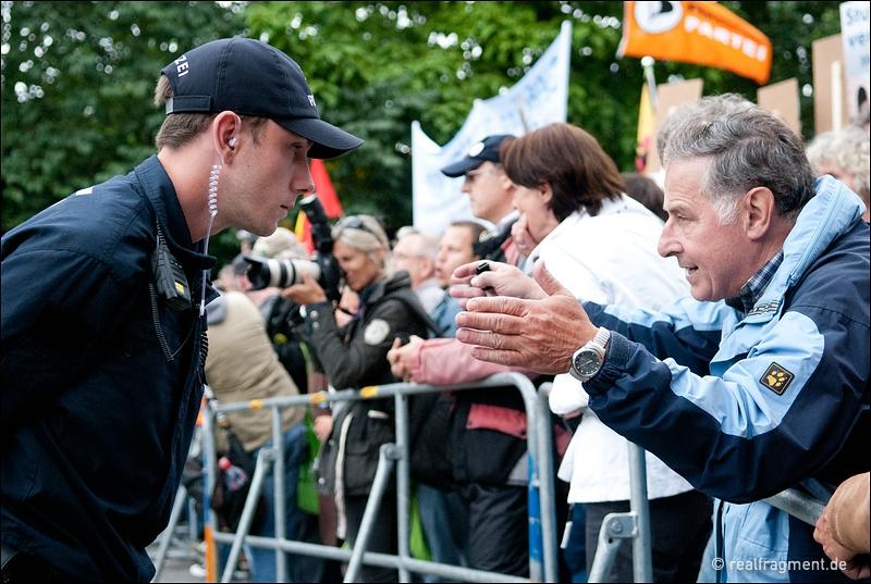 Ein Demonstrant diskutiert an einer Polizeiabsperrung nahe des Baugeländes mit einem Polizisten